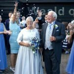 Bride in hand made dress and Groom celebrating with confetti