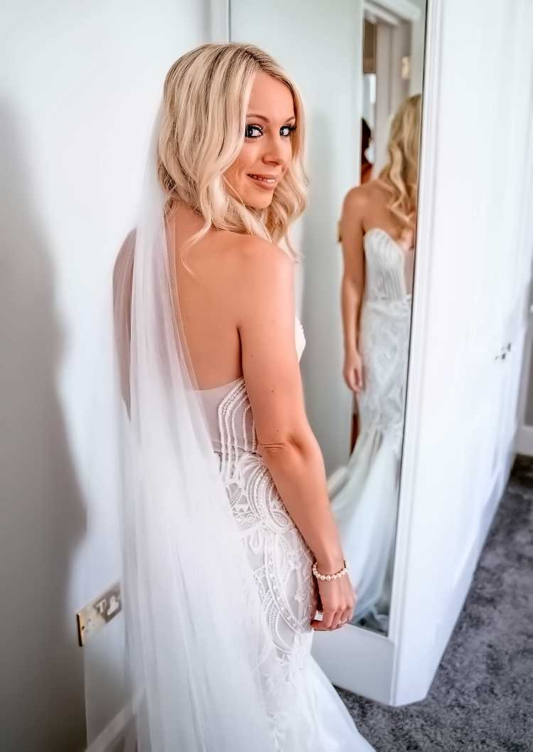Bride with vail standing in front of mirror