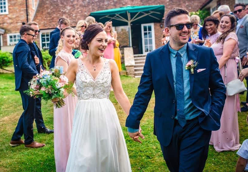 Bride and Groom walking with guests in the garden