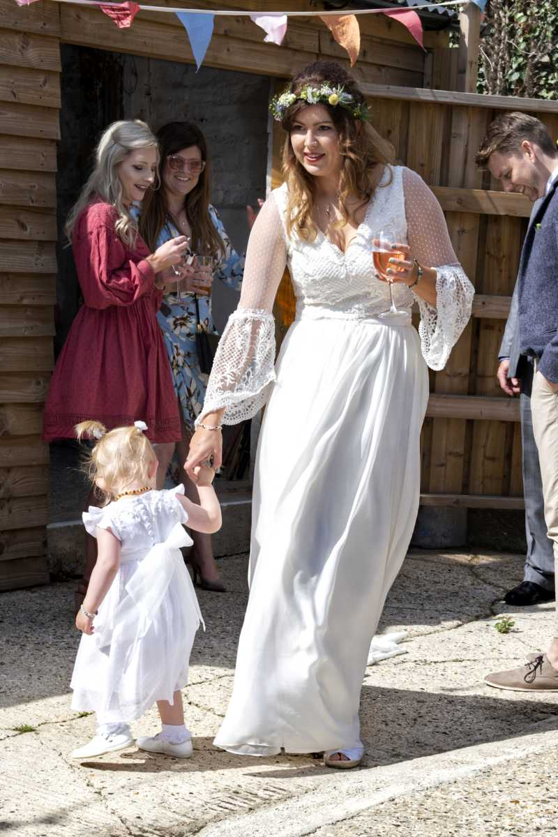 Bride in bespoke wedding dress with toddler in hand made dress