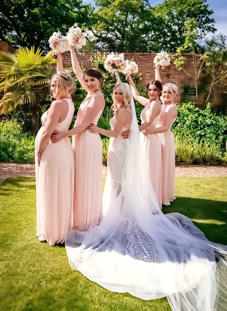 Bride with Bridesmaids holding flower bouquets aloft